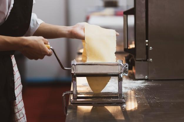 Chef, der teigwaren mit einer maschine, selbst gemachte frische teigwaren macht