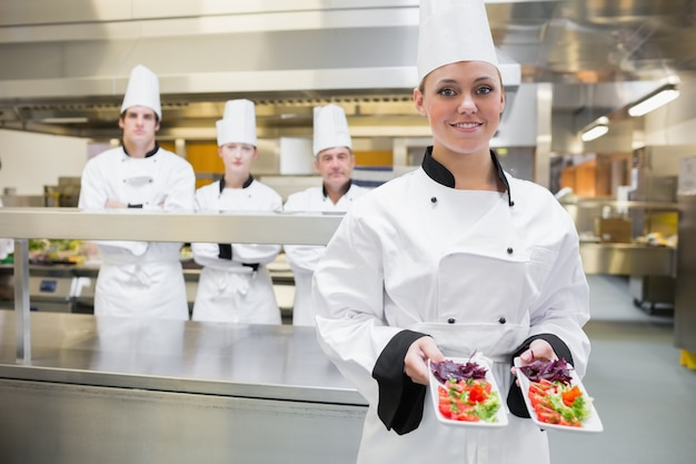 Chef, der zwei salate in der küche darstellt