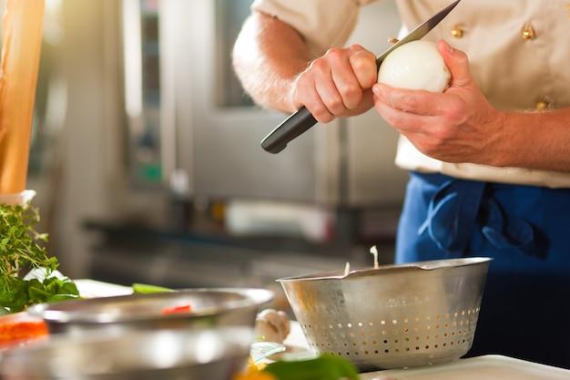 Chef, der zwiebel in der restaurant- oder hotelküche vorbereitet