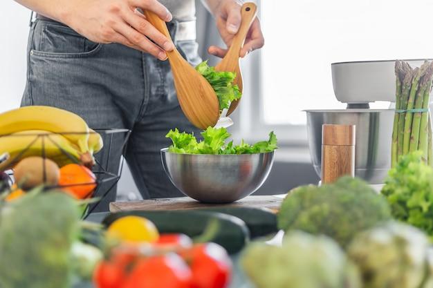 Chef des jungen mannes, der gesunden salat kocht