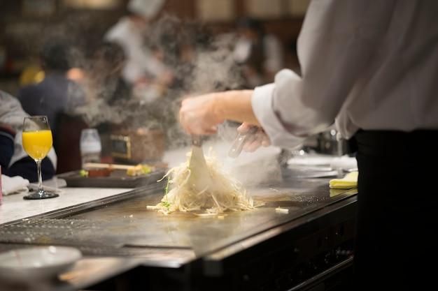 Chef des selektiven fokus, der teppayaki für kunden kocht