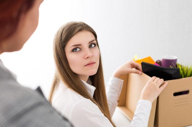 Chef entlässt einen mitarbeiter. niedergeschlagene entlassene büroangestellte, die ihren chef ansieht und ihre sachen in einen karton packt
