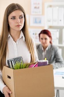 Chef entlässt einen mitarbeiter. niedergeschlagener entlassener büroangestellter mit einer kiste voller habseligkeiten