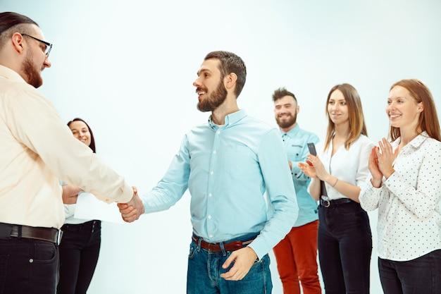 Chef genehmigt und gratuliert jungen erfolgreichen mitarbeiter