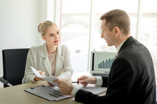 Chef geschäftsmann, der ernsthaft über bericht mit weiblicher angestellter am schreibtisch im büro spricht