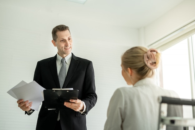 Chef geschäftsmann, der über bericht mit weiblicher angestellter am schreibtisch im büro spricht