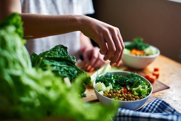 Chef gießt frühlingszwiebeln in eine schüssel mit den grünen erbsen, gurken, karotten, kopfsalat und dill, die auf einer tabelle stehen