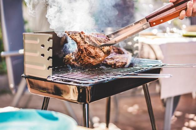 Chef-grill-t-bone-steaks beim grillabendessen im freien - mann, der fleisch für eine familiengrillmahlzeit draußen im hinterhofgarten kocht