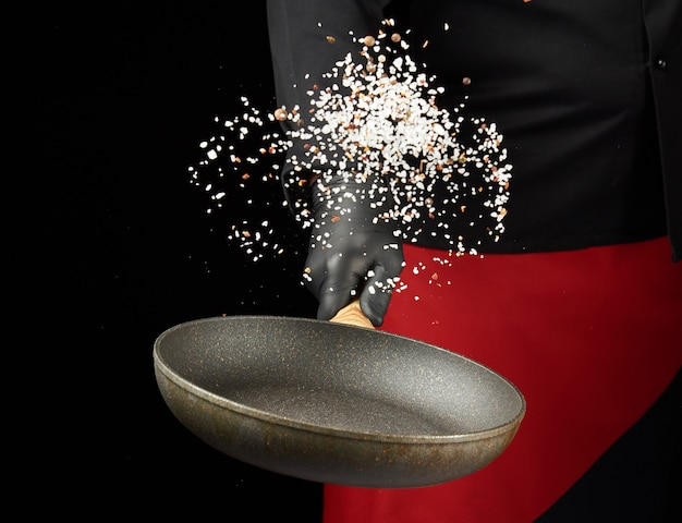 Chef hält eine runde pfanne und wirft die mischung aus gewürzen und weißem salz auf