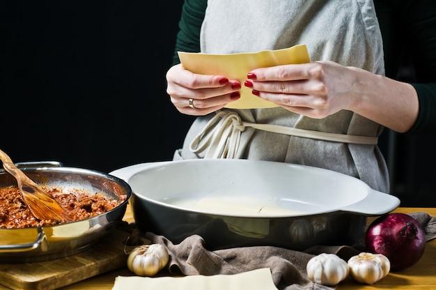 Chef hände machen eine lasagne