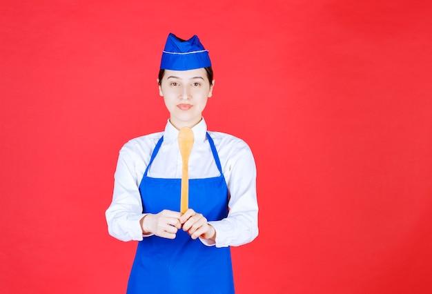 Chef in der blauen schürze, die einen hölzernen löffel hält.
