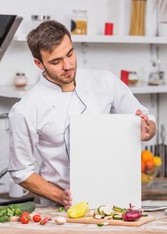 Chef in der küche, die papierschablone zeigt