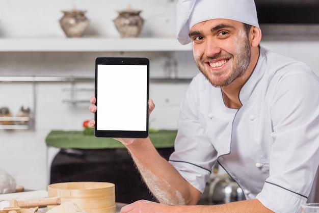 Chef in der küche mit tablettbildschirmschablone