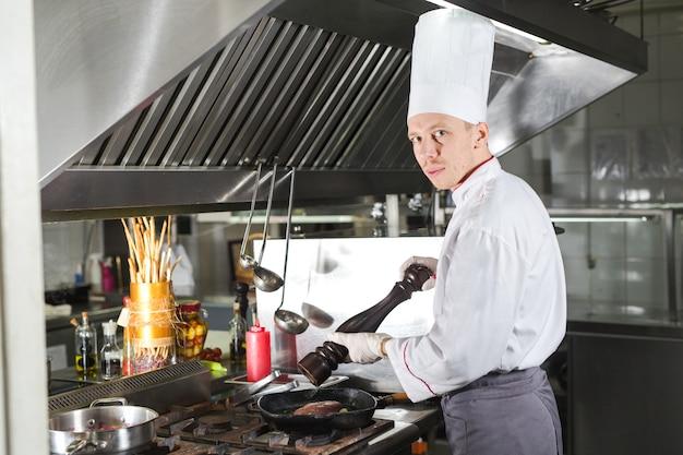 Chef in der restaurantküche am herd mit pfanne, kochend