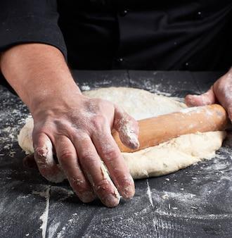 Chef in einer schwarzen tunika rollt einen teig für eine runde pizza