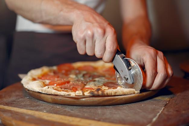 Chef in einer weißen uniform bereiten eine pizza zu