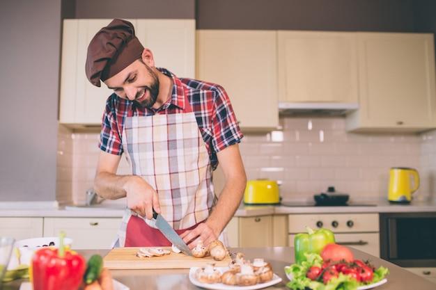 Chef in pron steht am tisch in der küche und schneidet pilze mit einem messer. er schaut sich diesen vorgang an und lächelt. guy ist positiv. er kocht und bereitet essen zu.