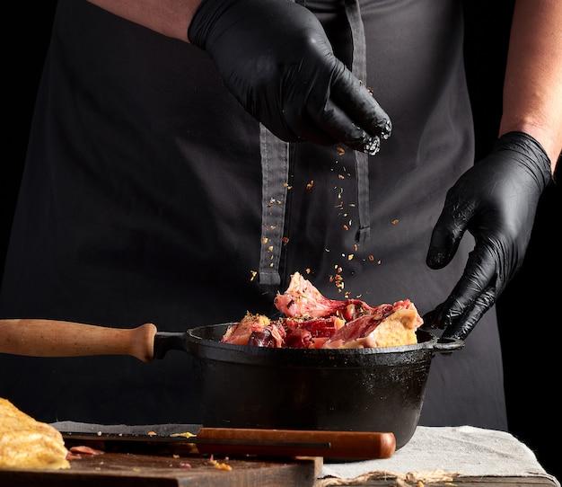 Chef in schwarzen uniform- und latexhandschuhen, die rohes hühnerfleisch in einer schwarzen roheisenbratpfanne, kochend würzen