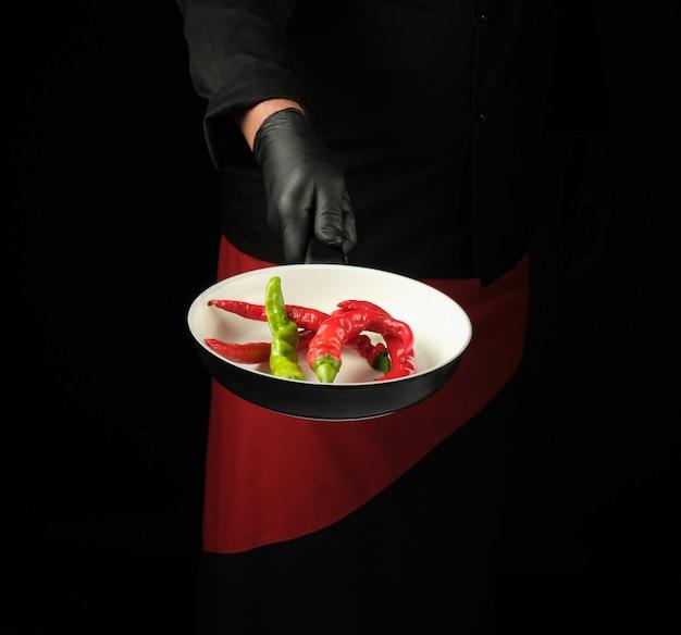 Chef in schwarzer uniform und roter schürze hält eine runde pfanne mit frischen chilischoten