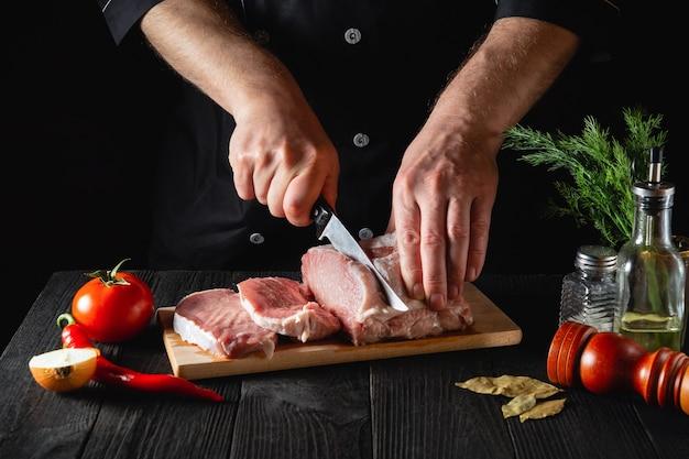 Chef metzger schneidet schweinefleisch mit messer in der küche und kocht essen