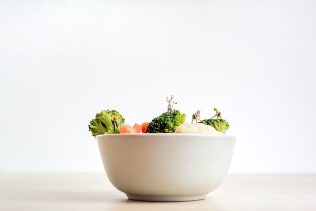 Chef mit bauern in einer riesigen schüssel salat