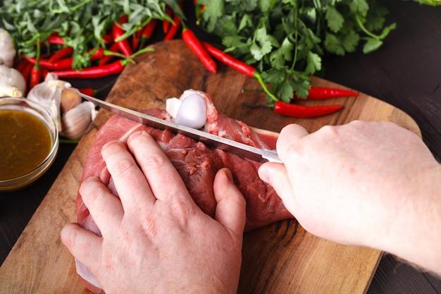 Chef mit einem messer in der hand schneidet frischfleisch auf einem tisch