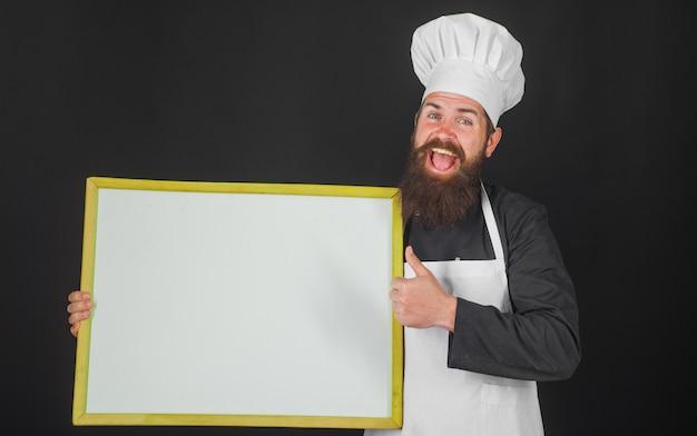 Chef mit leerer menütafel. lächelnder koch oder bäcker zeigt daumen nach oben. werbung. kopieren sie platz für text.