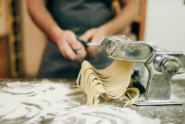 Chef mit messer in der hand, die frische hausgemachte fettuccine in der nudelmaschine auf hölzernem küchentisch kocht