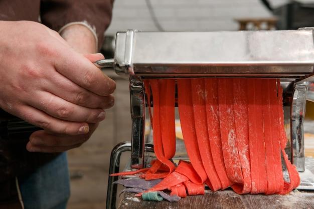 Chef mit nudelmaschine kocht roten nudelteig