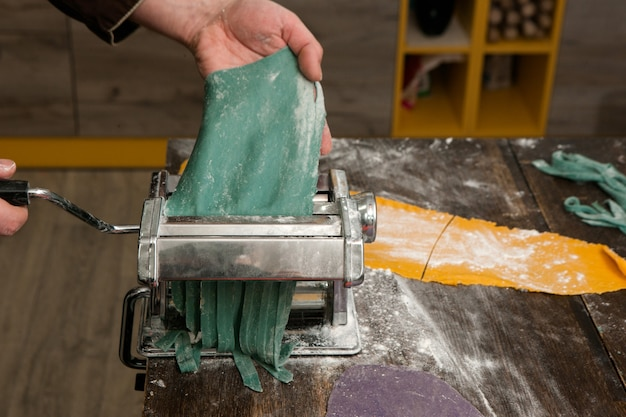 Chef mit nudelmaschine macht blauen teig für nudeln auf holztisch