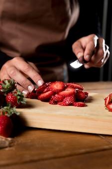 Chef mit schürze, die erdbeeren hackt