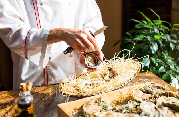 Chef öffnet frische auster in einem restaurant