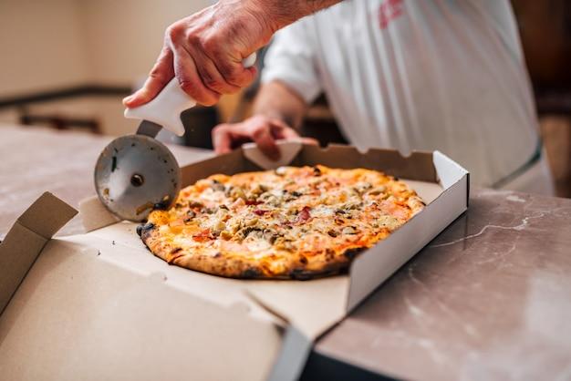 Chef schneiden pizza zum mitnehmen.