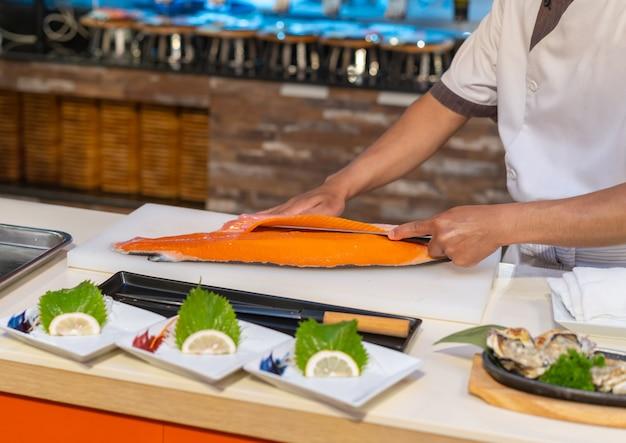 Chef schneidet lachs für sashimi, japanisches essen