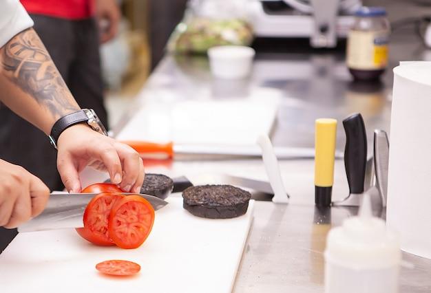 Chef schneidet tomaten für burger im küchenrestaurant