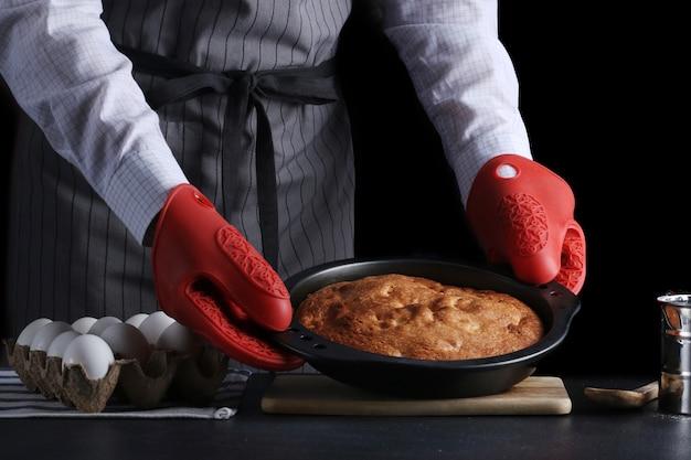 Chef serviert den kuchen auf dunklem hintergrund