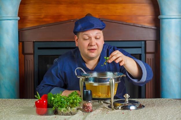Chef sitzt mit einem topf suppe und fügt die letzte zutat hinzu.
