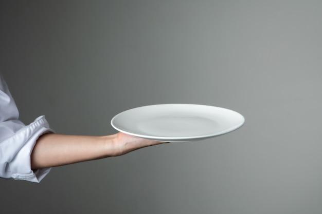 Chef uniform mit weißen leeren teller begrüßen geschenk gericht restaurant promotion