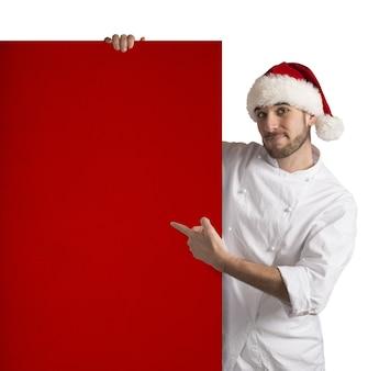 Chef zeigt eine rote plakatwand von weihnachten