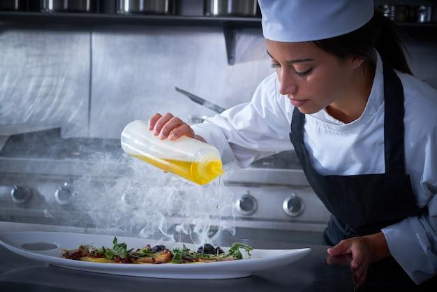 Cheffrau, die in der küche mit rauche arbeitet