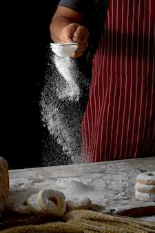 Chefhände, die brotteig und schaumgummiringe zubereitend besprühen