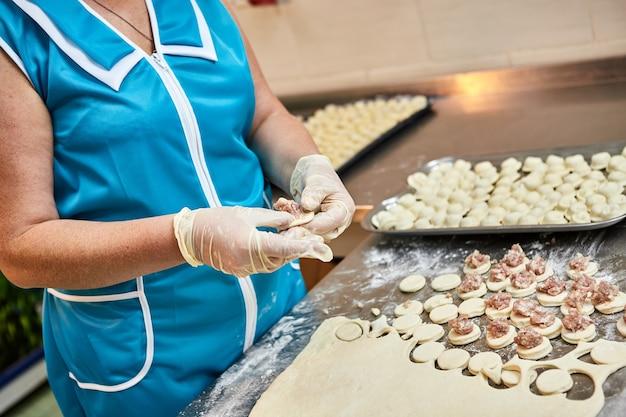 Chefhände formen knödel auf dem hintergrund von schneidebrettern mit handgemachten ravioli und khinkali, die mit mehl auf einem tisch bestreut sind. leckeres hausgemachtes essen.