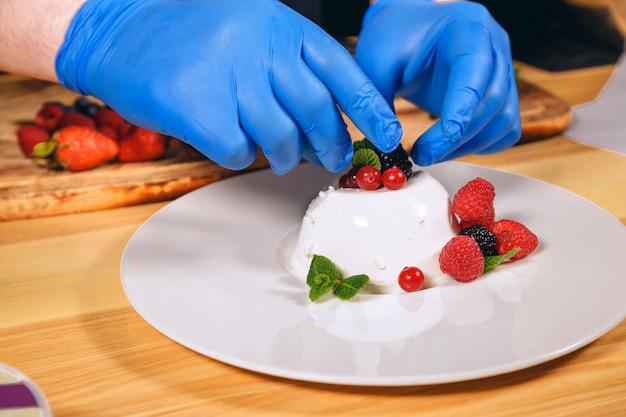 Chefhände mit den blauen handschuhen gekocht