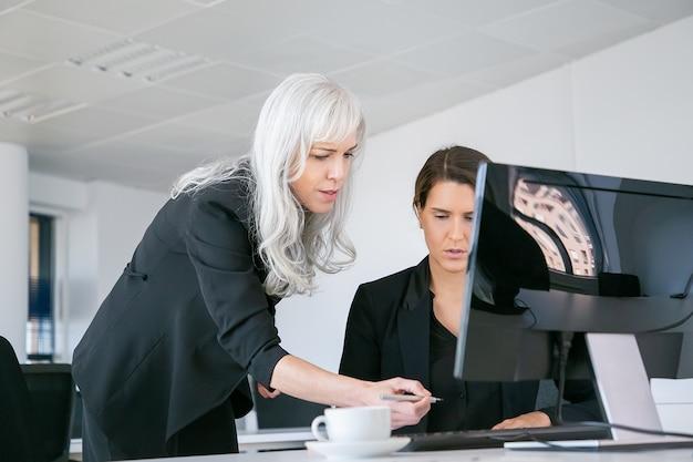 Chefin bringt unterschrift auf managerbericht an. geschäftsfrauen sitzen und stehen am arbeitsplatz mit monitor und kaffeetasse. geschäftskommunikationskonzept