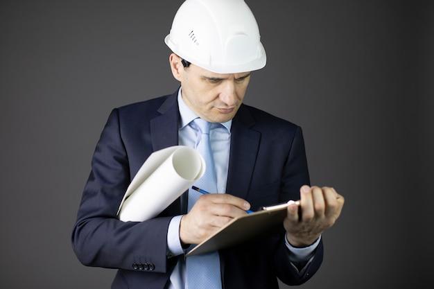 Chefingenieur für schutzhelm macht sich notizen in der zwischenablage mit blaupausenrolle