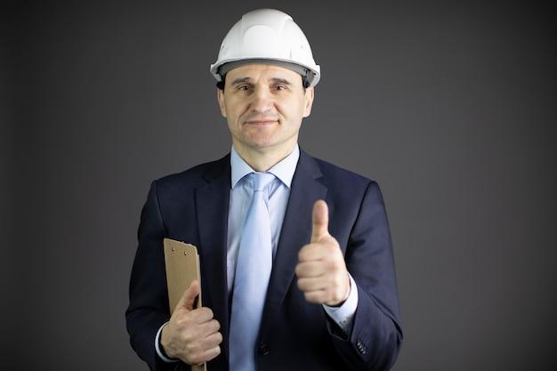 Chefingenieur im schutzhelm mit zwischenablage, die wie zeichen mit daumen nach oben zeigt