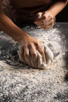 Chefkoch bedeckt teig mit mehl, um ihn weniger klebrig zu machen