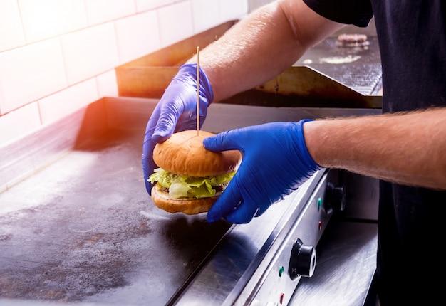 Chefkoch bereitet burger am küchengrillofen zu. restaurant.
