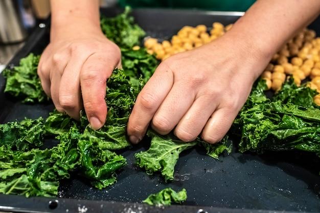 Chefkoch bereitet einen teller mit kohl und kichererbsen vor.