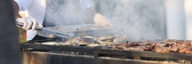 Chefkoch bereitet fleisch auf dem grill im freien zu